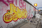 "Where young Germans once risked their lives, graffiti and tags now adorn the concrete surfaces of original sections of the Berlin wall at the East Side Gallery on Muhlenstrasse, Berlin. The site is the former border between Communist East and West Berlin during the Cold War. The Berlin Wall was a barrier constructed by the German Democratic Republic (GDR, East Germany) starting on 13 August 1961, that completely cut off (by land) West Berlin from surrounding East Germany and from East Berlin. The Eastern Bloc claimed that the wall was erected to protect its population from fascist elements conspiring to prevent the ""will of the people"" in building a socialist state in East Germany. In practice, the Wall served to prevent the massive emigration and defection that marked Germany and the communist Eastern Bloc during the post-World War II period."