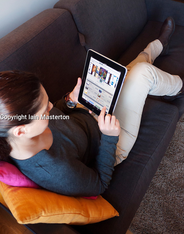 Woman using iPad computer tablet at home to look at Application or Apps store from Apple