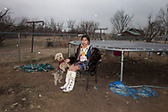 Hayden Sheridan, 10, plays dress-up in her aunt Hannah's jingle dress as it starts to snow. Homemade regalia will often stay in the family for years being passed down from generation to generation. El Reno, Oklahoma 2016. (photo by Alexandra Dietz)
