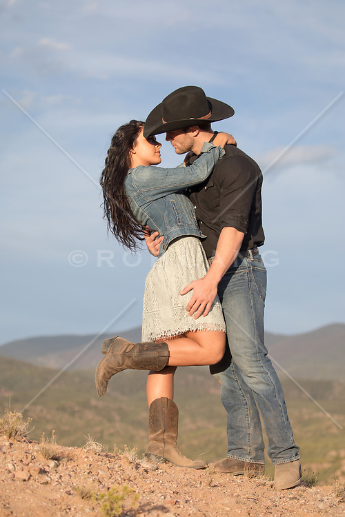 cowboy and a girl about to kiss outside on a mountain range