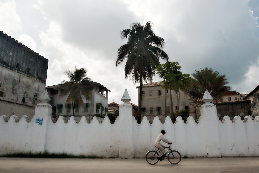 "A man rides his bike past a wall displaying the Arab architectural influence in Stone Town, Zanzibar. Stone Town, also known as Mji Mkongwe (Swahili for ""old town"") is the oldest part of Zanzibar City and a UNESCO World Heritage Site."