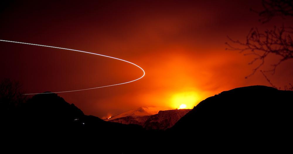 """An eruption on Fimmvorduhals in the south of Iceland lights up the cloudy night while a search and rescue helicopter makes a u-turn to go pick up an injured """"volcano tourist"""" on his way from viewing the eruption. Eldgosið á Fimmvörðuhálsi lýsir upp himininn á meðan þyrla Landhelgisgæslunnar snýr við til að sækja slasaðan """"gosfara"""" á gönguleiðina á Fimmvörðuháls."""