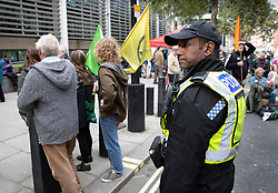© Licensed to London News Pictures. 09/10/2019. London, UK. A police officer from the Hampshire Constabulary stands outside The Home Office as Extinction Rebellion activists take part in a third day of protests in central London. The climate change group intend to blockade the Westminster area for two weeks to demand that the government takes immediate and decisive action on climate change. Photo credit: Peter Macdiarmid/LNP