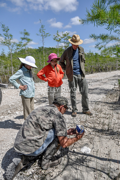 A swamp buggy tour guide shows a family how to pour plaster casts of a panther's tracks they found in Big Cypress National Preserve.