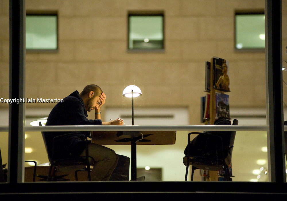 Man studying at desk in main city public library in Malmo Sweden