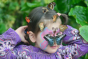 © Licensed to London News Pictures. 19/01/2014. Wisley,  UK Momiji Radscheit.   Sisters Momiji (3) and Sakura (12) Radscheit pose with butterflies at RHS Wisley today 19th January 2014. Hundreds of exotic butterflies will be released into the Glasshouse at RHS Garden Wisley, in Surrey, to create a tropical paradise this winter. Butterflies in the Glasshouse runs from Sat 18 Jan – Sun 9 March 2014. Photo credit : Stephen Simpson/LNP