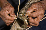Weaving split cane Matape<br /> Macushi people,<br /> Fairview Amerindian village<br /> Iwokrama Reserve<br /> GUYANA. South America<br /> The matape is used to strain boiled yucca to remove toxins.