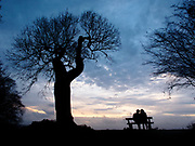 A couple huddle together on a park bench to watch the sunset over the River Thames from Richmond Park London