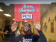 28 DECEMBER 2019 - DES MOINES, IOWA: QUAN TRIMBLE, a field organizer for Pete Buttigieg, puts up a Buttigieg sign at Urban Dreams, before a Pete Buttigieg meet and greet. Buttigieg talked to a crowd of about 75 people at Urban Dreams, an African-American community empowerment center in Des Moines. It was a part of Buttigieg's continuing outreach to African-American voters. Buttigieg, the mayor of South Bend, Indiana, is running to be the Democratic nominee for President in the 2020 election. Iowa traditionally holds the first presidential selection event of the 2020 election cycle. The Iowa Caucuses are on Feb. 3, 2020.           PHOTO BY JACK KURTZ