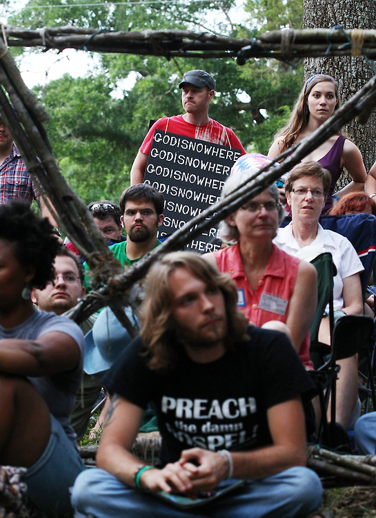 Members of VOID, an experimental faith collective in Waco, Texas, wore signs that could be read multiple ways at the Wild Goose Festival at Shakori Hills in North Carolina June 23, 2011.  (Photo by Courtney Perry)