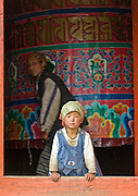 "A woman turns a Mani Thungkyur (a large prayer wheel, which may contain religious books) while a girl looks out the door, at Pangboche Gompa (temple), Nepal. Buddhism became firmly established in Nepal's Khumbu District (home of the Sherpa people) about 350 years ago by the power and influence of Lama Sangwa Dorje. He established the oldest monastery in Khumbu at Pangboche (plus many other small hermitages). Sagarmatha National Park was created in 1976 and honored as a UNESCO World Heritage Site in 1979. Published in ""Light Travel: Photography on the Go"" book by Tom Dempsey 2009, 2010."
