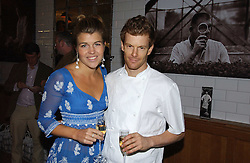 TOM AIKENS and AMBER NUTTALL at the opening party for Tom's Kitchen - the restaurant of Tom Aikens at 27 Cale Street, London SW3 on 1st November 2006.<br />