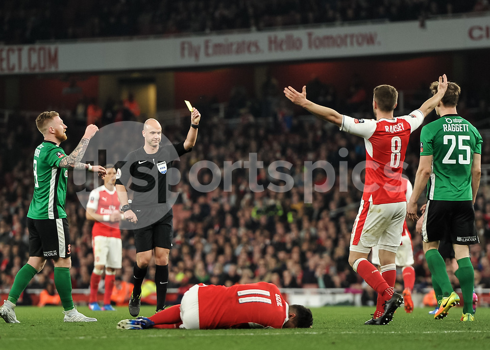 Sean Raggett of Lincoln City is shown the yellow card by Referee Anthony Taylor during the The FA Cup sixth round match between Arsenal and Lincoln City at the Emirates Stadium, London, England on 11 March 2017. Photo by Vince Mignott.