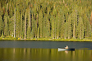 A flyfisherman enjoys the solitude of an alpine lake north of Crested Butte, Colorado in mid-summer.
