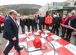 """Campaigners from Shelter Scotland raise awareness of their campaign """"Homelessness - Far From Fixed"""" outside the Scottish Parliament in Edinburgh. They are joined by carol singers from Corstorphine Primary School, a Christmas tree and a giant snakes and ladders board game - Chance Not Choice - which illustrates how life chances affect people's ability to keep a roof over their head.<br /> <br /> Pictured: James Dornan (SNP) playing Chance Not Choice with Evan Jones from Costorphine Primary School throwing the dice"""