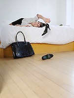 Young woman lying on bed throwing high heeled shoes on floor