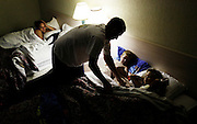 Chad Perillard, center, tucks his children Preston, 3, left, and Piper, 6, right, into bed while their mother Jennifer Audette, left, watches, in a room at the Red Roof Inn in East Naples, where the family had been living for a month. Greg Kahn/Staff