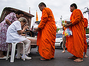 """21 JULY 2013 - BANGKOK, THAILAND:   An elderly woman sits in a chair to give monks alms at Wat Benchamabophit on the first day of Vassa, the three-month annual retreat observed by Theravada monks and nuns. On the first day of Vassa (or Buddhist Lent) many Buddhists visit their temples to """"make merit."""" During Vassa, monks and nuns remain inside monasteries and temple grounds, devoting their time to intensive meditation and study. Laypeople support the monastic sangha by bringing food, candles and other offerings to temples. Laypeople also often observe Vassa by giving up something, such as smoking or eating meat. For this reason, westerners sometimes call Vassa the """"Buddhist Lent.""""        PHOTO BY JACK KURTZ"""