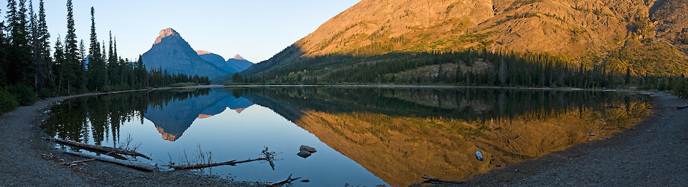 "Sinopah Mountain (8271 feet or 2521 meters) reflects in Pray Lake at sunrise in Glacier National Park, Montana, USA. Published in ""Light Travel: Photography on the Go"" book by Tom Dempsey 2009, 2010. (Panorama stitched from 4 overlapping images.) Since 1932, Canada and USA have shared Waterton-Glacier International Peace Park, which UNESCO declared a World Heritage Site (1995) containing two Biosphere Reserves (1976). Rocks in the park are primarily sedimentary layers deposited in shallow seas over 1.6 billion to 800 million years ago. During the tectonic formation of the Rocky Mountains 170 million years ago, the Lewis Overthrust displaced these old rocks over newer Cretaceous age rocks. Glaciers carved spectacular U-shaped valleys and pyramidal peaks as recently as the Last Glacial Maximum (the last ""Ice Age"" 25,000 to 13,000 years ago). Of the 150 glaciers existing in the mid 1800s, only 25 active glaciers remain in the park as of 2010, and all may disappear by 2020, say climate scientists."