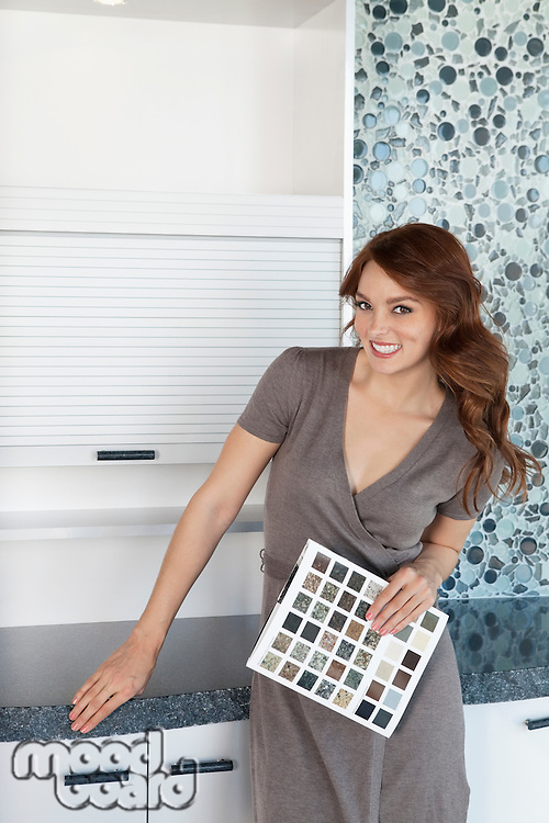 Portrait of beautiful young woman with color samples standing in contemporary kitchen