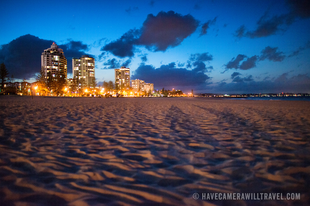 "Coolangatta's beach at dusk, with the skyline buildings in the background. Sometimes paired as ""Twin Towns,"" Coolangatta and Tweed Heads, on the southern end of the Gold Coast, straddle the Queensland-New South Wales border."