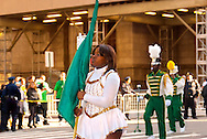 MARCH 17, 2011 - MANHATTAN: Marching in St. Patrick's Day Parade across from St. Patrick's Cathedral, teen girl holding green flag, with high school band, NYC.