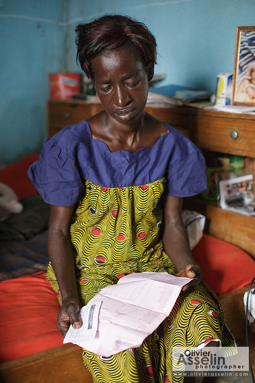 Adjua Yao, 45, who is HIV positive, holds her prescription for ARV drugs as she sits in a room of her sister's home in the Campement neighborhood of Abidjan, Cote d'Ivoire on Wednesday July 10, 2013. Adjua, a mother of five, is currently unemployed and lives with her sister. She's under ARV treatment and takes three pills a day.