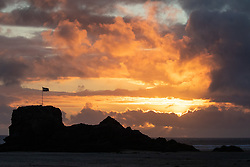 © Licensed to London News Pictures. 01/07/2020. Perranporth, UK. The sun sets behind Chapel Rock, on Perranporth beach, Cornwall. From this weekend, a large number of tourists are expected to arrive in Cornwall, as the regulations on COVID-19 (Coronavirus) are lifted. Photo credit : Tom Nicholson/LNP