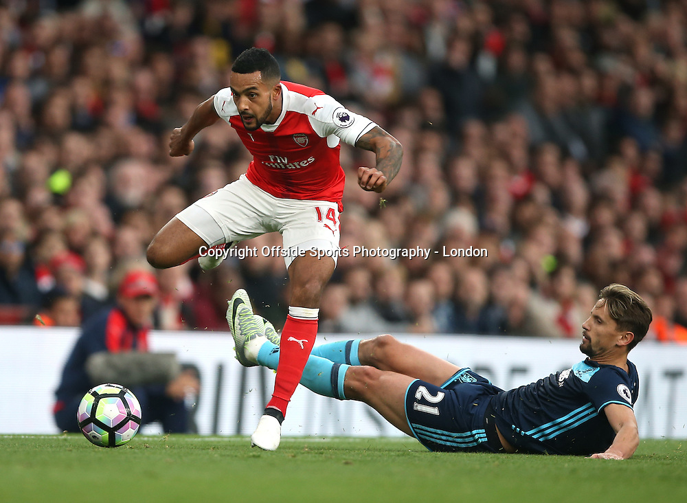 22 October 2016 Premier League Football - Arsenal v Middlesbrough :<br /> Theo Walcott leaps over the tackle of Gaston Ramirez of Middlesbrough.<br /> Photo: Mark Leech