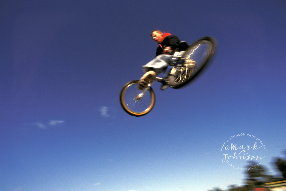 Australia, Queensland, Brisbane, teenage boy jumping BMX bike
