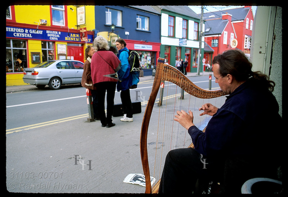Australian musician Andy Gowan plays Celtic harp outside the colorful shops and pubs of Dingle, Ireland.
