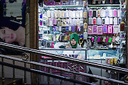 "A shot of a woman selling phone accessories in Kashgar, Xinjiang, China. The Xinjiang province is located in western China and named a ""Special Economic Zone in 2010. In the recent decades the centuries old architecture has been being slowly replaced and rebuilt with fortified concrete structures and surrounded by Chinese-style highrises."