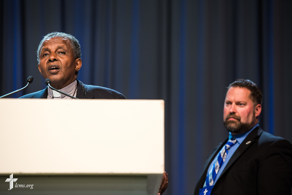The Rev. Dr. Berhanu Ofgaa, general secretary of the Ethiopian Evangelical Church Mekane Yesus, addresses the 66th Regular Convention of the Lutheran Church—Missouri Synod on Wednesday, July 13. Behind him is the Rev. Dr. Albert B. Collver III, director of church relations-assistant to the LCMS president. LCMS/Michael Schuermann