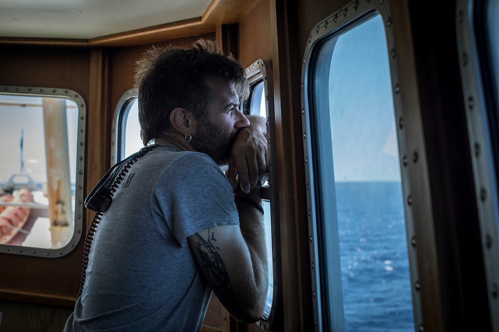 June 2017, Central Mediterranean. Looking for possible targets with the binoculars. NGO Proactiva Open Arms in their 20th rescue mission in the Central Mediterranean Sea on board of Golfo Azzurro vessel (photo Edu Bayer)