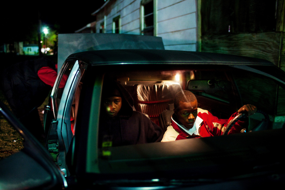 "Little Mike (L) and a friend sit in a car blasting tunes while another young man works on the speakers in the trunk after their friend Demetrius ""Butta"" Anderson's wake in the Baptist Town neighborhood of Greenwood, Mississippi on Thursday, November 4, 2010."