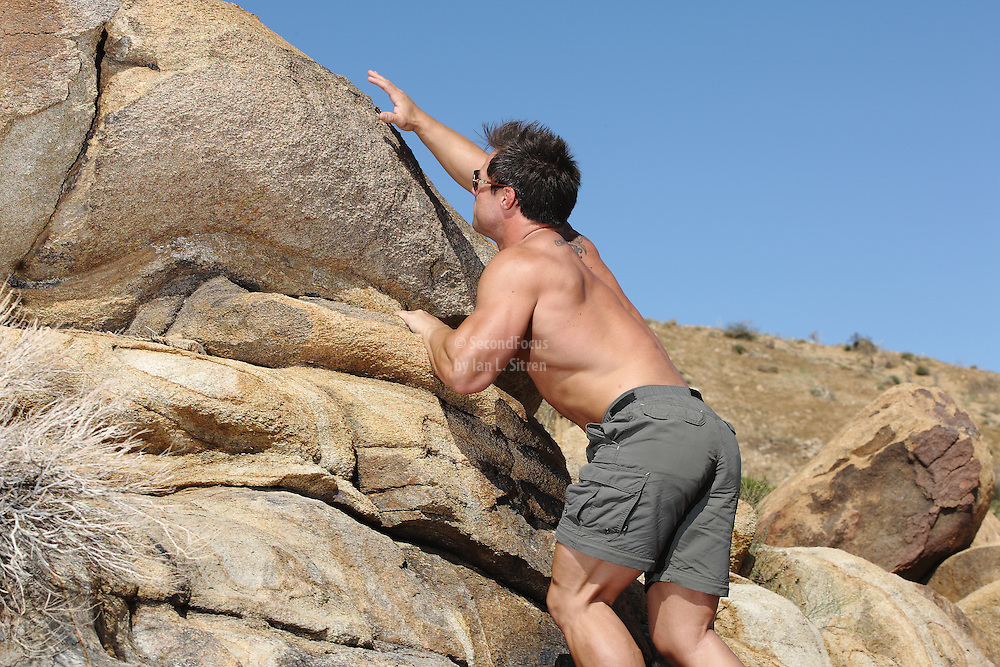 Bodybuilder Jake Sawyer trail running and climbing rocks for exercise and fun.