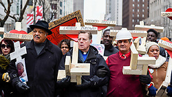 © Licensed to London News Pictures. 31/12/2016. Chicago, USA. Jesse Jackson (L) joins a Peace March, organised by Father Michael Pfleger (C) and builder of the crosses, Greg Zanis (R), taking place down Chicago's Magnificent Mile, Michigan Avenue, to honour the survivors and victims of the city's escalating gun violence.  Marchers carry a 2-foot-tall white wooden cross, each bearing the name of a person killed by gun violence in 2016.  With over 4,300 shootings and more than 750 people killed in 2016, these are the highest totals for 20 years and more than any other large U.S. city in 2016, according to news reports. Photo credit : Stephen Chung/LNP