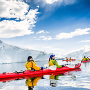 Kayakers glide through calm waters and admire the view at Neko Harbour, Antarctica.