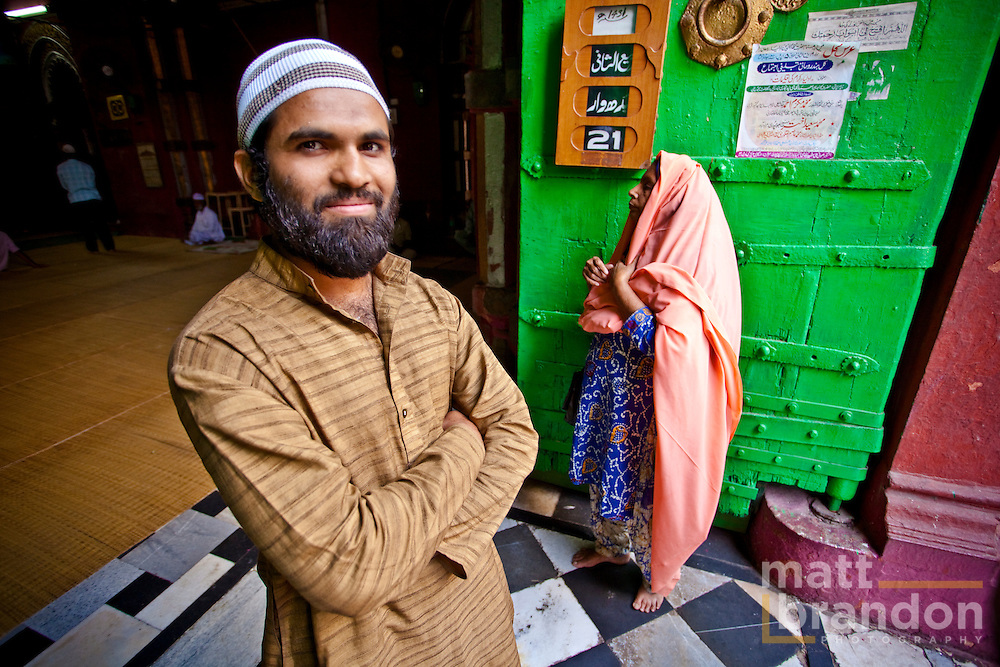 Muslim man stand in the doorway to the Allahudin Masque at the Nizamuddin Shrine.