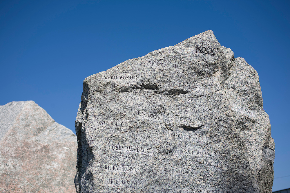 A granite rock in front of Rockingham Speedway bearing the names of all the winners from past NASCAR races and the new rock to the left.