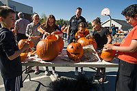Officer Daniel O'Neill looks on a group of 5th, 6th and 7th grade students as they carve thier pumpkins Thursday afternoon at Gilford Middle School for this weekend's Pumpkin Festival.  (l-r) Andrew McDonough, Charlotte Lehr, Kassie Gard, Officer O'Neill, Ellie Nicolas and Arturo Delgadillo-Garcia.  (Karen Bobotas/for the Laconia Daily Sun)