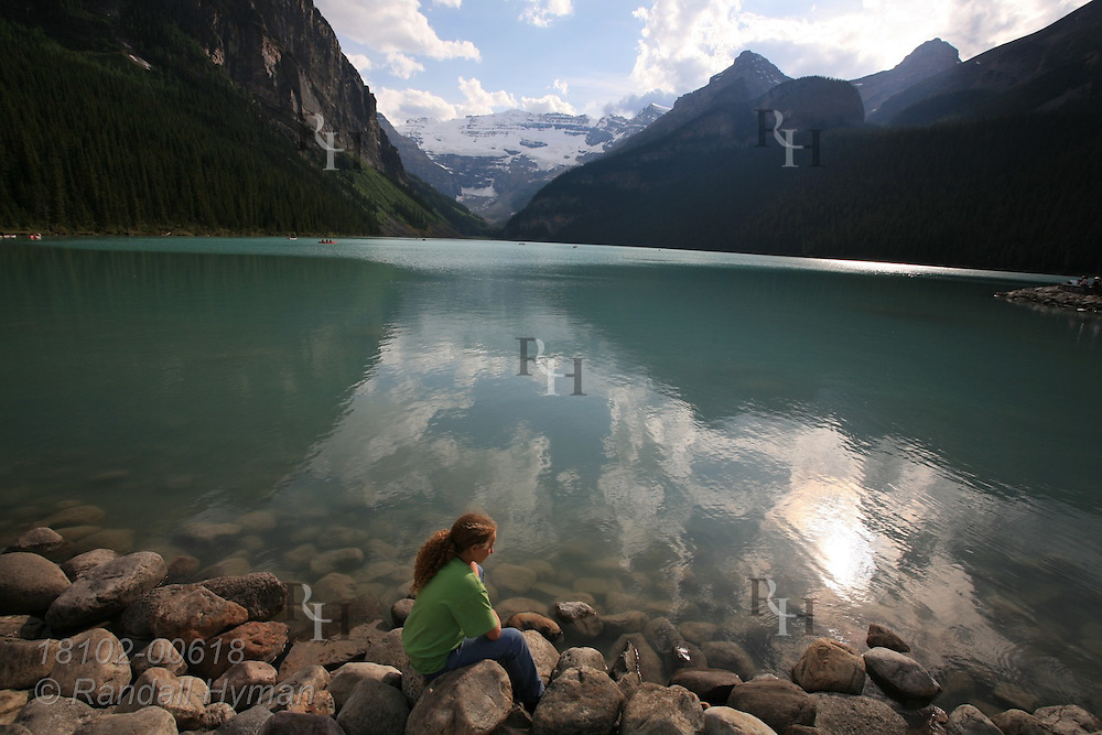Girl sits on rocky lakeshore enjoying the tranquility of Lake Louise amid the soaring mountains of Banff National Park in the Canadian Rockies; Alberta, Canada.
