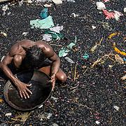 Sur les rives du Gange, au milieu des cendres et des détritus, un homme cherche des bijoux ou des dents en or qu'il pourra revendre.