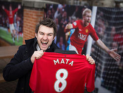 © Licensed to London News Pictures . 27/01/2014 . Manchester , UK . ANDY LEATHLEY (28) from Chorlton poses with his new shirt in front of iconic prints in front of Old Trafford . Fans with new MATA 8 shirts in front of Old Trafford Football Ground as it's announced that Spaniard Juan Mata ( Juan Manuel Mata García ) has signed for Manchester United  . Photo credit : Joel Goodman/LNP