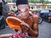 "18 AUGUST 2014 - BANGKOK, THAILAND:  A member of the Lehigh Leng Kaitoung Opera troupe applies his makeup before a performance at Chaomae Thapthim Shrine, a small Chinese shrine in a working class neighborhood of Bangkok. The performance was for Ghost Month. Chinese opera was once very popular in Thailand, where it is called ""Ngiew."" It is usually performed in the Teochew language. Millions of Chinese emigrated to Thailand (then Siam) in the 18th and 19th centuries and brought their culture with them. Recently the popularity of ngiew has faded as people turn to performances of opera on DVD or movies. There are still as many 30 Chinese opera troupes left in Bangkok and its environs. They are especially busy during Chinese New Year and Chinese holiday when they travel from Chinese temple to Chinese temple performing on stages they put up in streets near the temple, sometimes sleeping on hammocks they sling under their stage. Most of the Chinese operas from Bangkok travel to Malaysia for Ghost Month, leaving just a few to perform in Bangkok.      PHOTO BY JACK KURTZ"