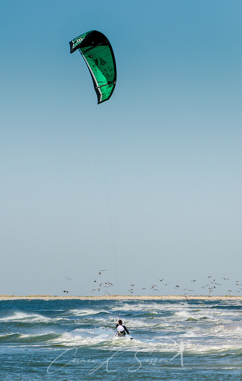 Mathieu Junco kitesurfs with a F-One Delta C-shaped Bandit Six kite, October 18, 2015, in Dauphin Island, Alabama. Junco, from France, began kitesurfing five years ago. Windy conditions on the island brought surfers out in droves, but many, like Junco, found that the brisk northerly winds made kitesurfing challenging on the south side of the island. Kitesurfing began in France in the 1980's and became a mainstream water sport in 1999, combining aspects of wakeboarding, windsurfing, surfing, and paragliding. More than 1.5 million people participate in the global sport. (Photo by Carmen K. Sisson/Cloudybright)