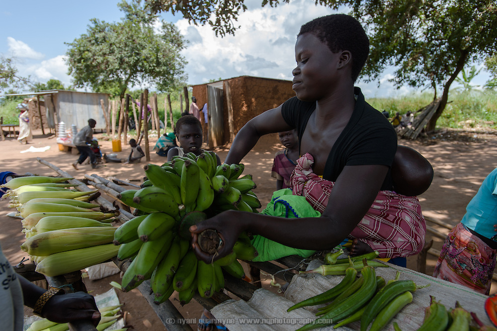 A woman selling plantains at the small village market at Ifoho Boma in Imurok Payam in Eastern Equatoria, South Sudan, on 9 August 2014. The market is the only source of income for some families in the community, and the paucity of goods on sale underscores both the lack of produce available, and the weak purchasing power of village residents.