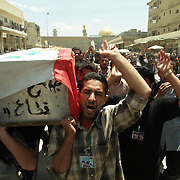 5 April 2004..Najaf, Iraq...Funeral for soldier of Medhi Army...Moqtada al Sadr remains holed up in the Holy city of Najaf..The US forces have an arrest warrant out for him and had vowed to bring him in dead or alive. At present the US forces have remained on the outskirts of towm and al Sadr's private militia the Medhi Army control the center of the city...There are almost daily clashes between coalition troops and local militia...Ahmad Abdul Zahara aged 30 was killed during such a clash. Fellow militia and friends carried his body through the streets before taking it for burial, they carried pictures of al Sadr and chanted slogans in support of him.