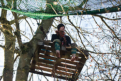 Harefield, UK. 19 January, 2020. A tree-climbing activist sits on a pallet suspended from a tree in the Colne Valley wildlife protection camp. Activists from Extinction Rebellion, Stop HS2 and Save the Colne Valley attending a 'Stand for the Trees' event timed to coincide with tree felling work for HS2 have retaken the camp from which a small group of Save the Colne Valley activists had been evicted by bailiffs acting on behalf of HS2 over the previous week and a half. 108 ancient woodlands are set to be destroyed by the high-speed rail link.