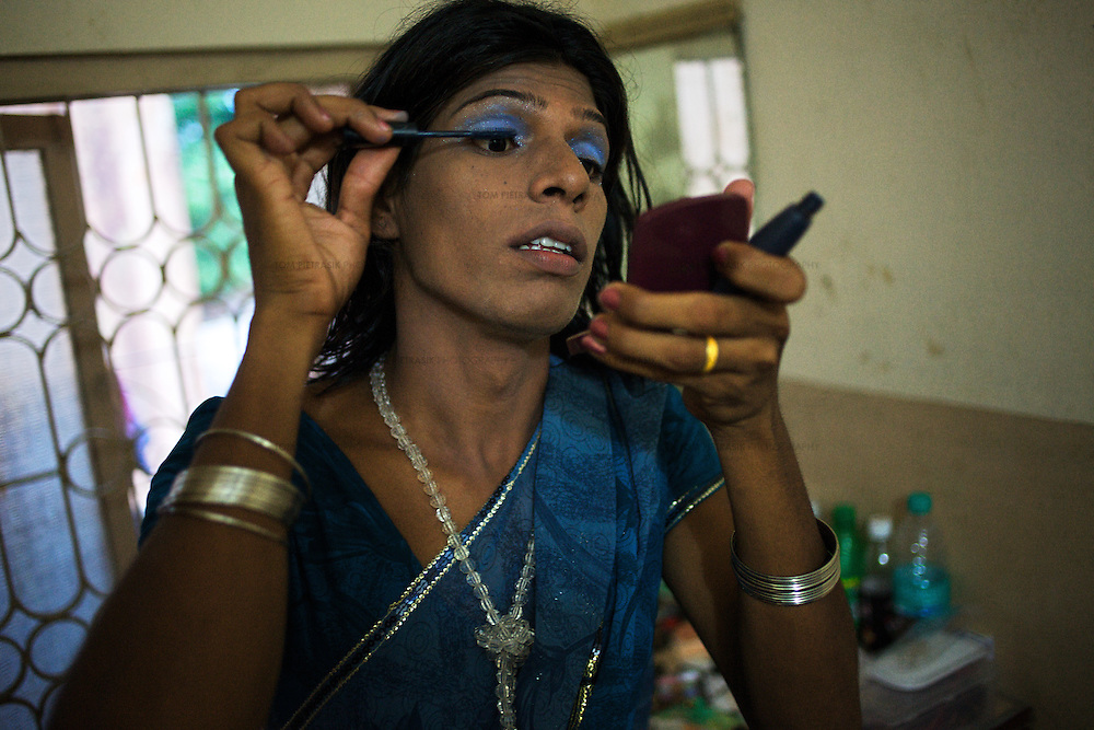 A transgender prepares herself  for an evening with friends in the town of Vilappuram during the week-long transgender gathering.  ..India's transexual community has a recorded history of more than four thousand years. Many consider the The Third Sex, also known as Aravanis, to posses special powers allowing them to determine the fate of others. As such, they are not only revered but despised and feared too. Resigned to the fringes of society, segregated and excluded from most occupations, many Aravanis are forced to turn to begging and sex work in order to earn a living. ..The annual transgender festival in the village of Koovagam, near Vilappuram, offers an escape from this often desolate existence. For some, the week-long partying and frenetic sex trade that culminates in the Koovagam festival is about fulfilling lustful desires. For others, the gathering provides a chance for transgenders to bond, share experiences, join the wider homosexual gay-community and coordinate their campaign for recognition and tackle the challenge of HIV/AIDS. ..It is the Indian state of Tamil Nadu that the eighty-thousand-strong Aravani community has made advances in their fight for rights. In 2009, the Tamil Nadu state government began providing sex-change surgery free of cost. The state has also offers special third-gender ration cards, passports and reserved seats in colleges. And 2008 the launch of Ippudikku Rose, a Tamil talk-show fronted by India's first transgender TV-host and the release of a mainstream Tamil film staring an Aravani in the lead-role. ..These advances clearly signal a victory for south India's transgenders, but they have also exposed deep divisions within the community. There is a very real gulf that separates the majority poor from their potentially influential but often reticent, upper-class sisters. ..Photo: Tom Pietrasik.Vilappuram District, Tamil Nadu. India.May 2009